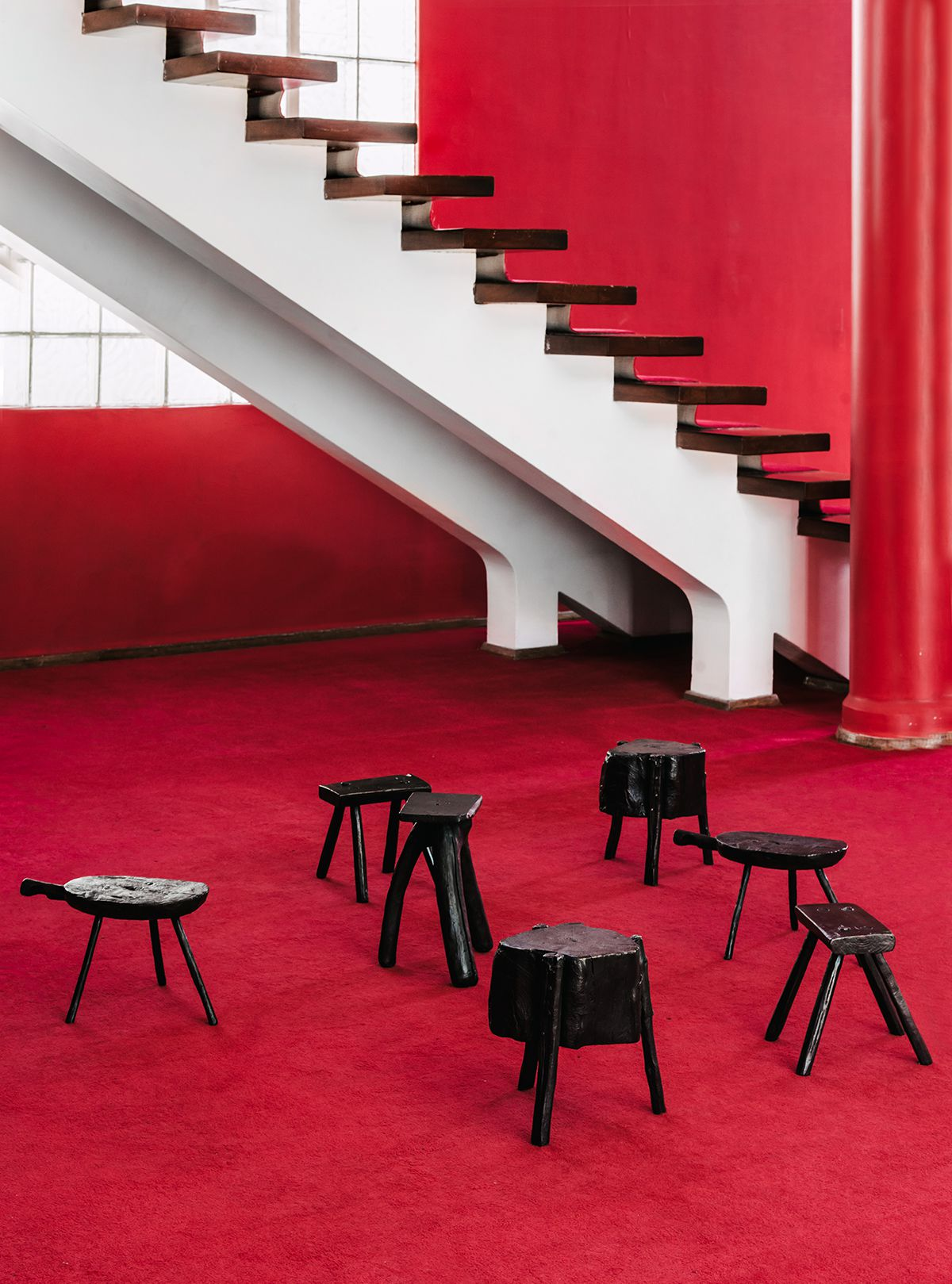 A room with red walls and red floors. A group of black stools is on the floor. There is a white staircase with black steps against one of the walls.
