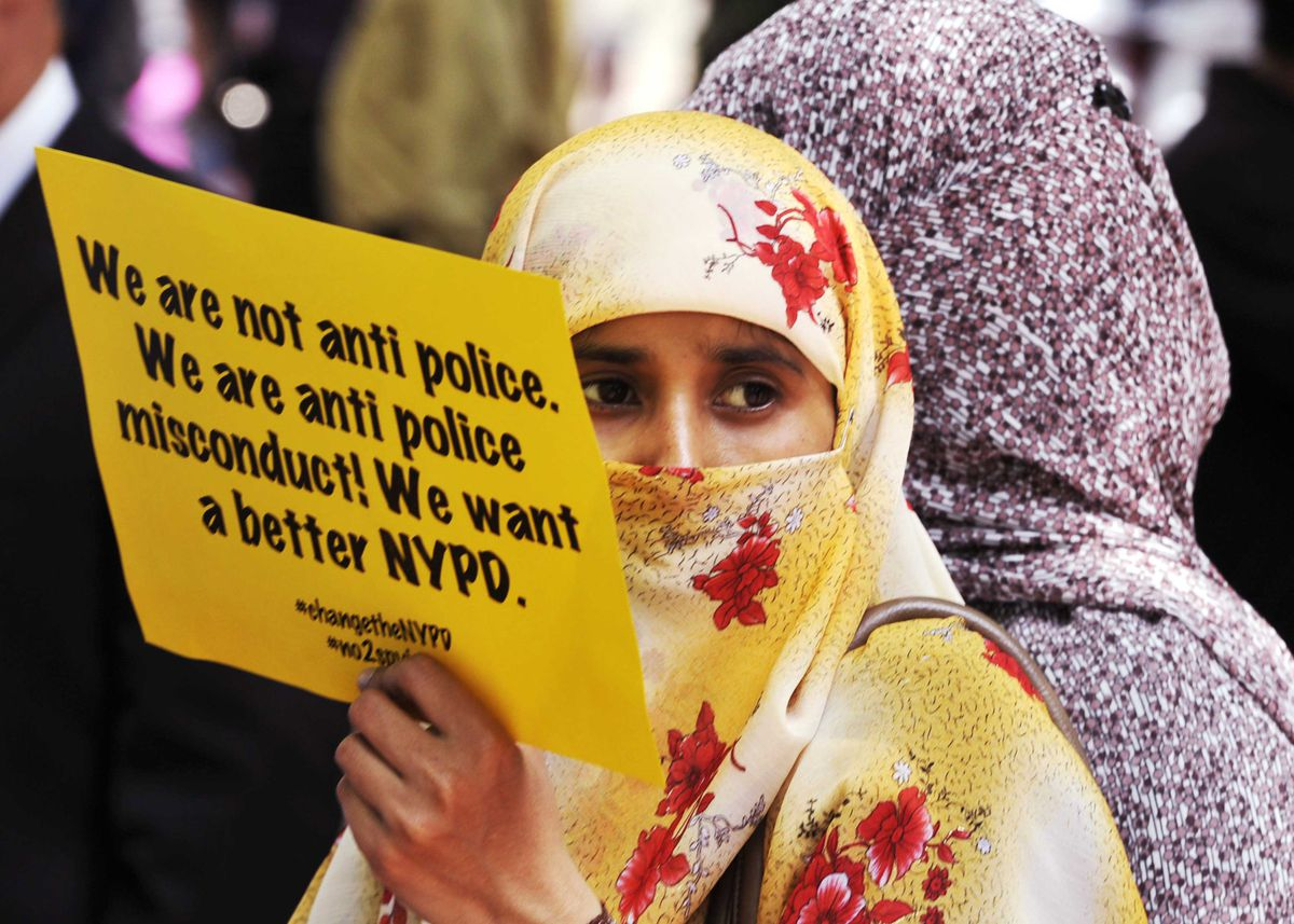 """A woman in a hijab holds a sign that reads """"We are not anti police. We are anti police misconduct! We want a better NYPD."""""""