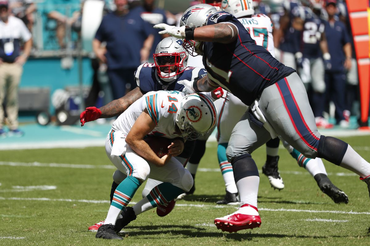 Miami Dolphins quarterback Ryan Fitzpatrick ducks as New England Patriots outside linebacker Elandon Roberts and defensive tackle Danny Shelton close in for a sack during a Sunday, Sept. 15, 2019, game in Florida.