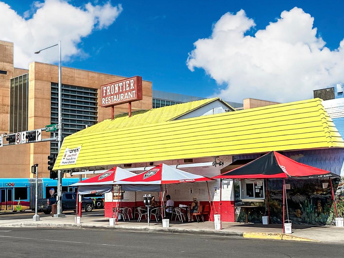 A restaurant with a bright roof and vintage sign, with outdoor seating beneath a few awnings along its side