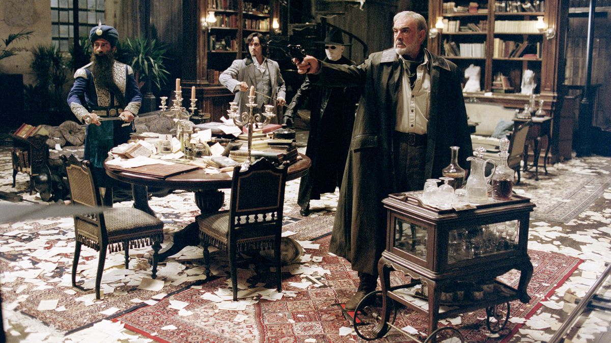 Three men stand in a library that has paper all over the floor.
