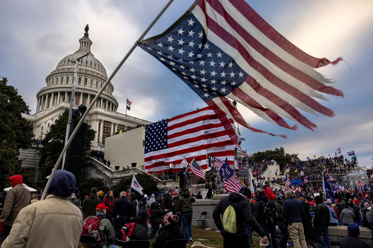 A rioter holds a tattered, upside-down United States flag alongside several other Trump supporters during the attempted insurrection of the United States Capitol on January 6, 2021.