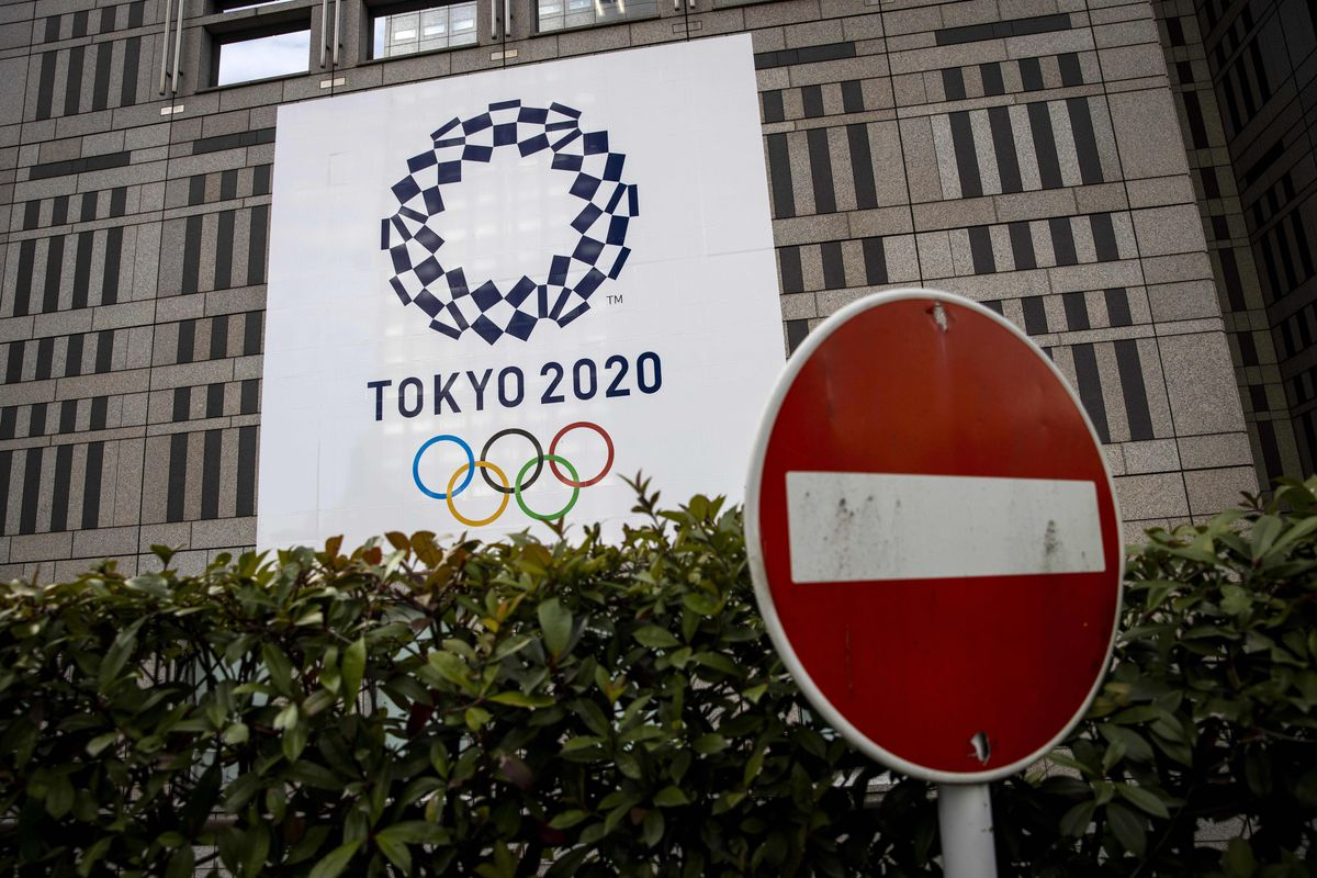 A traffic sign is seen next to an official Tokyo 2020 Olympic Games banner hanging on the Tokyo Metropolitan Government Building on January 22, 2021.