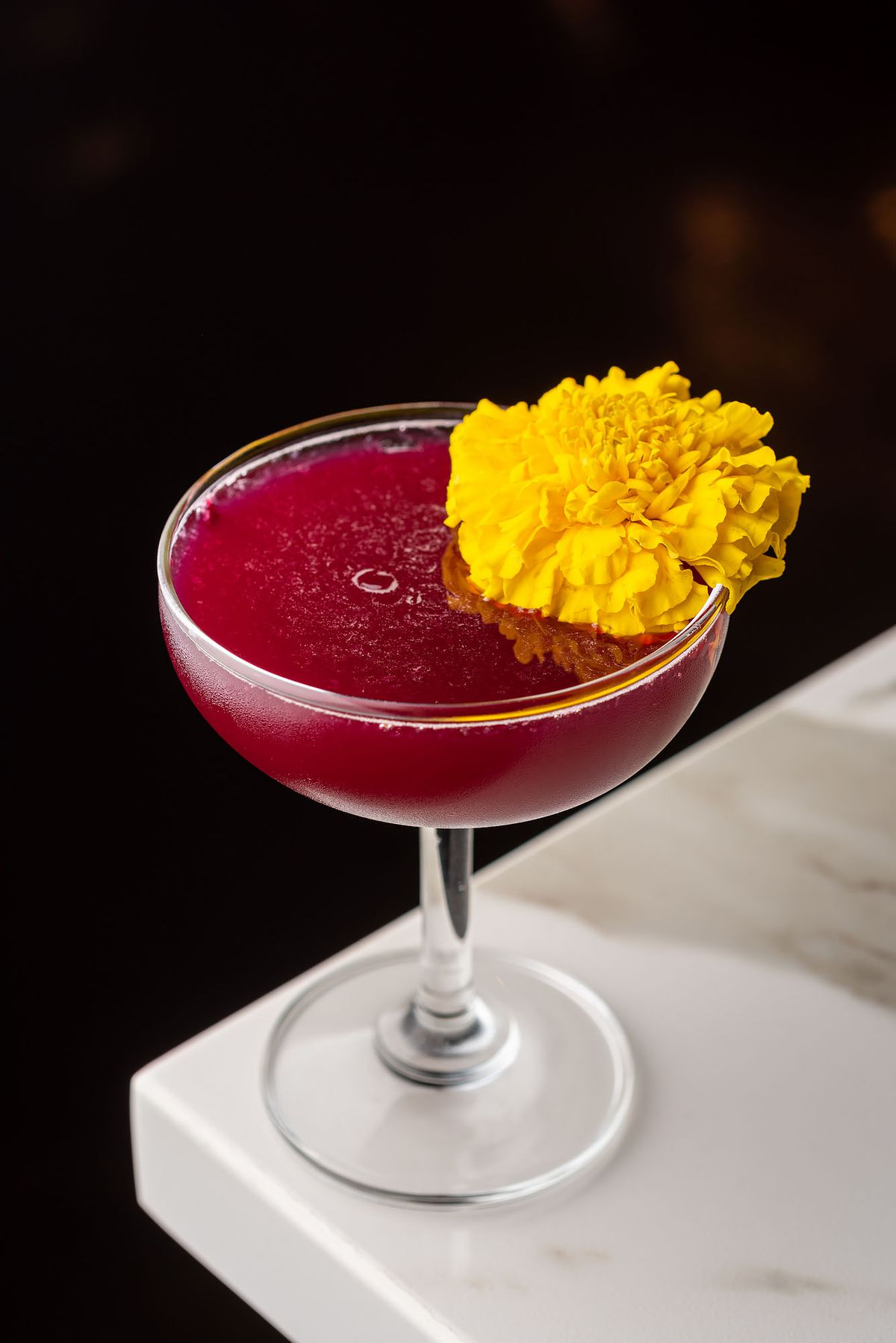 A deep red cocktail with a yellow flower sitting on the rim.