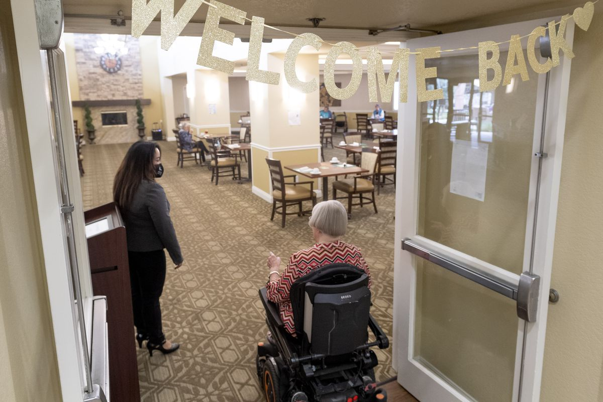 """A person in a wheelchair enters a care home's dining room under a """"welcome back"""" banner."""