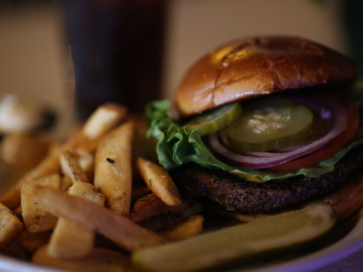 a burger with pickles, red onion, and lettuce with fries
