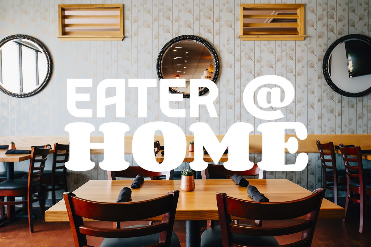 """""""Eater @ Home"""" logo pasted over image of empty restaurant dining room, with wooden tables set with wooden chairs"""