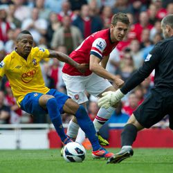 Arsenal's Aaron Ramsey, center, shoots past Southampton's Nathaniel Clyne, left, but fails to score during their English Premier League soccer match at the Emirates stadium, London, Saturday, Sept. 15, 2012.