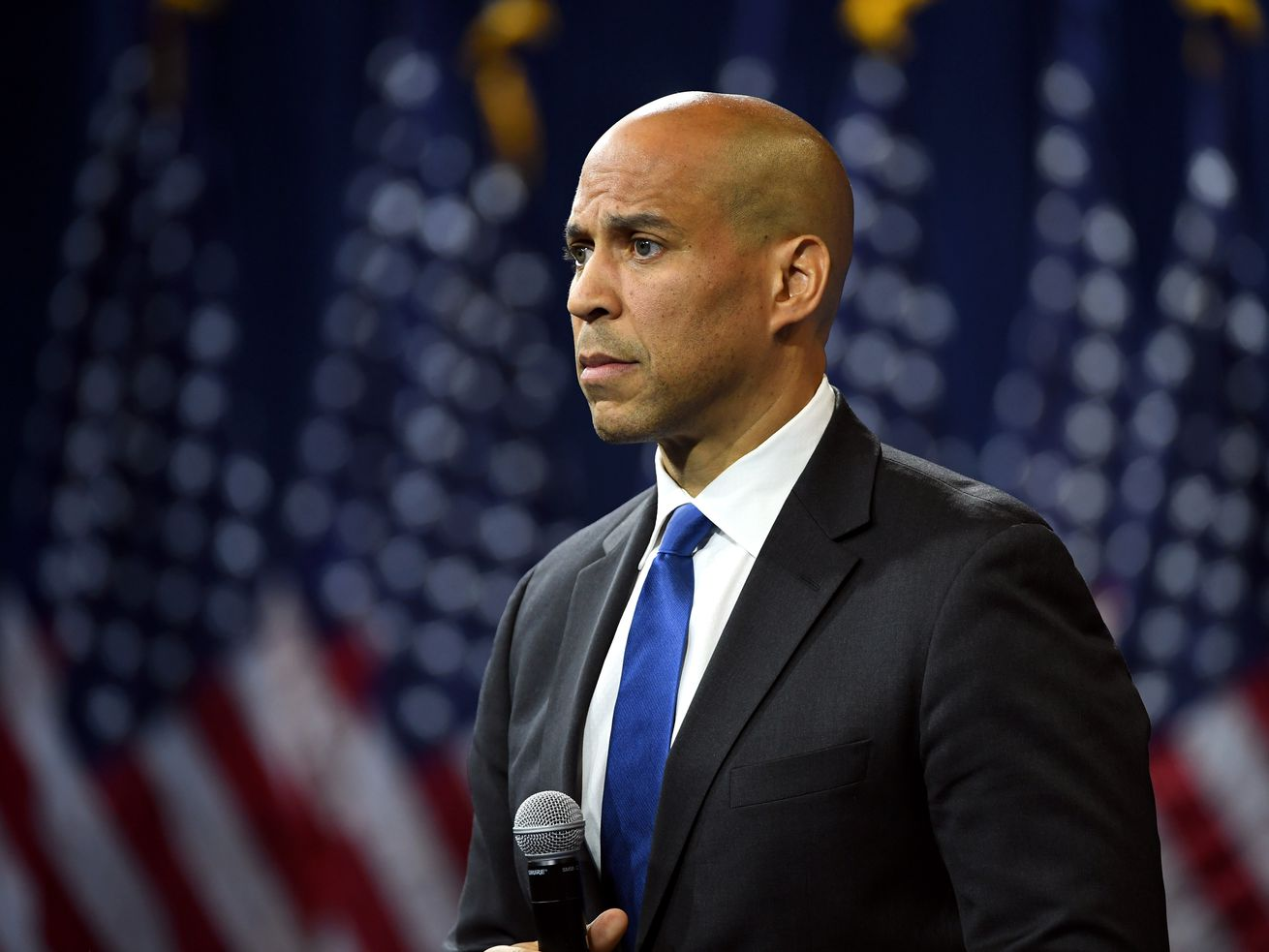 Senator Cory Booker holds a microphone and stands onstage in front of several American flags.