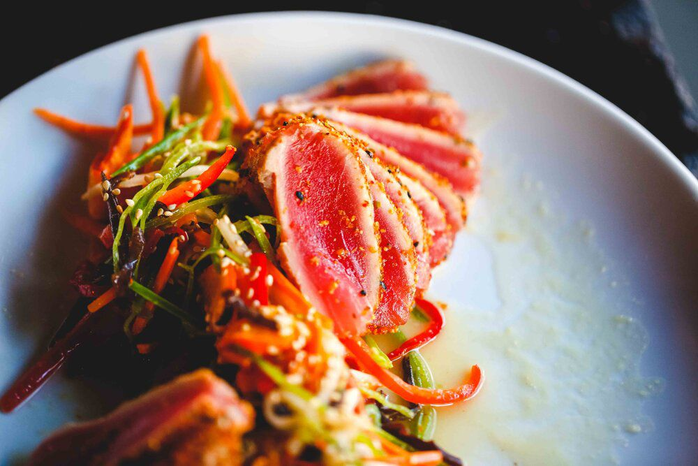 A plate of vegetable slaw with a stack of thinly sliced seared tuna.
