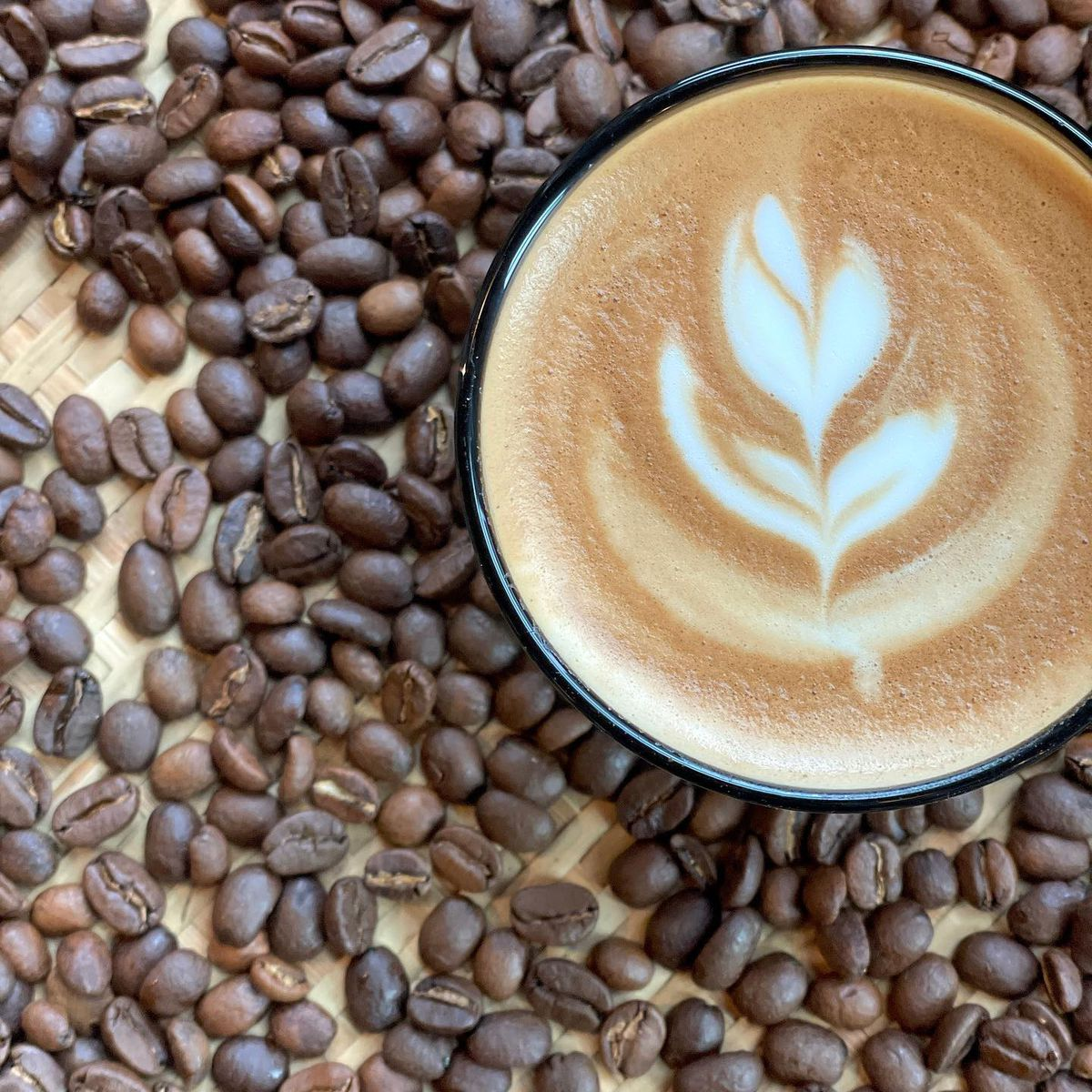 Top-down view of a latte with a flower design against the backdrop of coffee beans