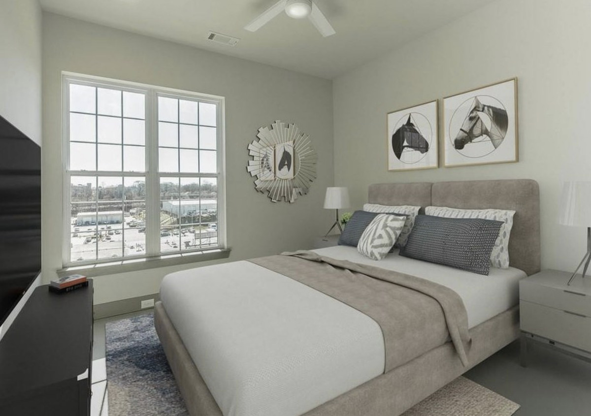 Bedroom with large window in the back, and a bed, nightstands with lamps, and TV on dresser in the front.