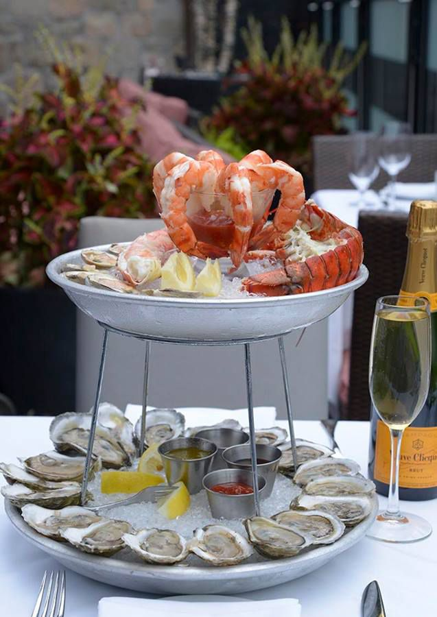 A two-level seafood tower is full of oysters, shrimp cocktail, half lobster, and more. It sits on a white tablecloth-covered table on a restaurant patio, a glass of champagne to the side.