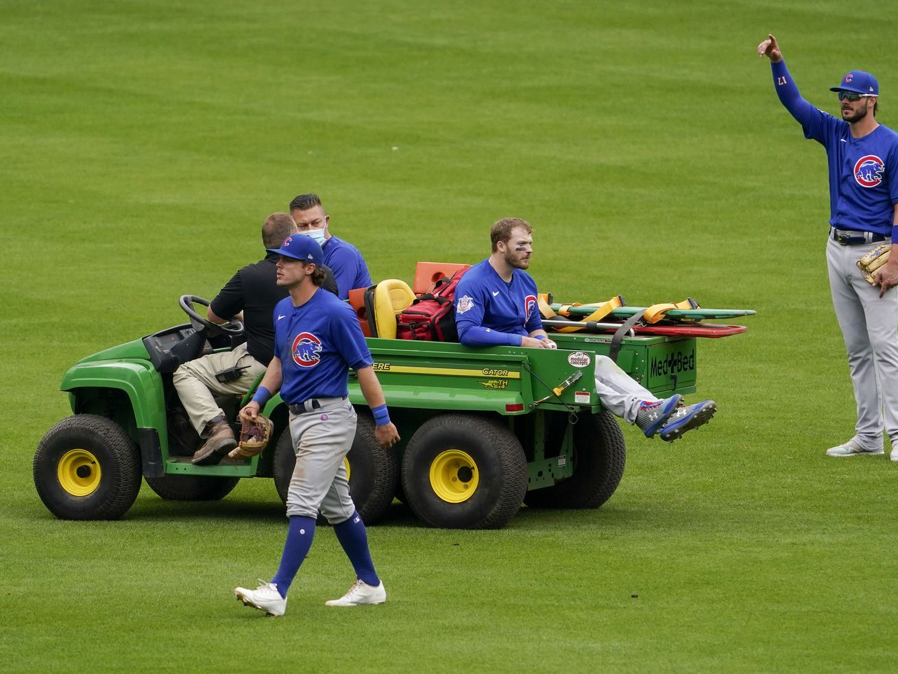 Cubs center fielder Ian Happ, center, is carted off after a collision with teammate Nico Hoerner, foreground, in the eighth inning of Sunday's game.