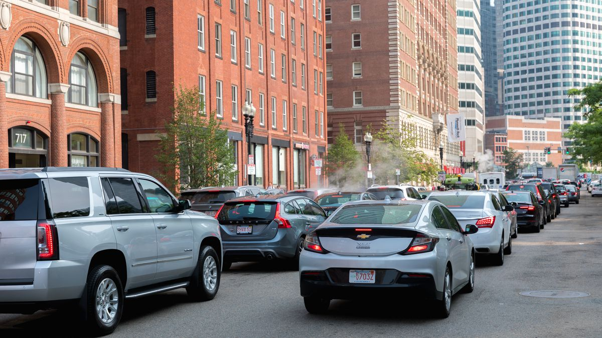 Cars bunched up on a downtown street with buildings on either side.