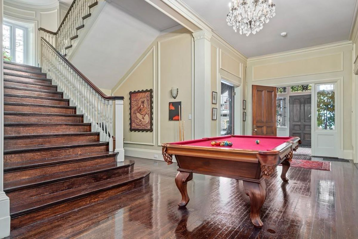 A pool table in a large entry foyer, with a staircase next to it.