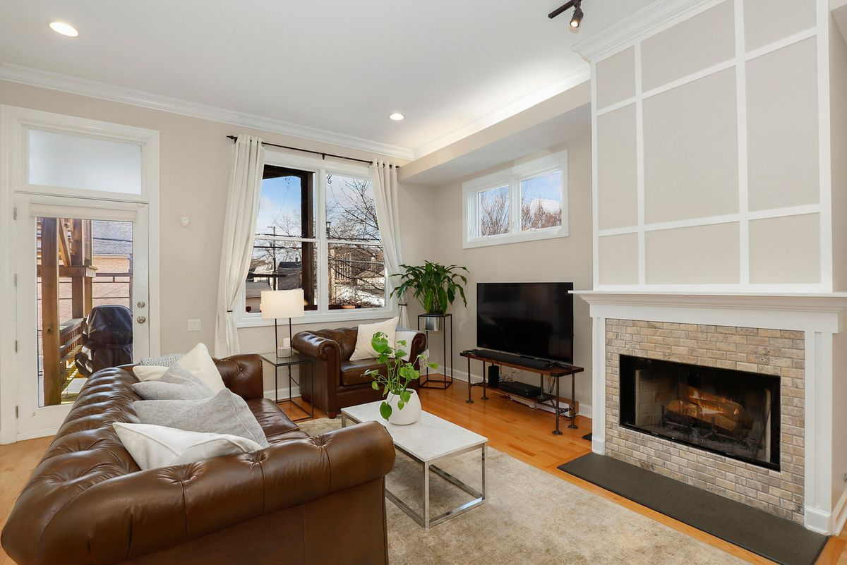 The main living area with a fireplace and tile mantel. There is a brown leather couch and access to a deck.