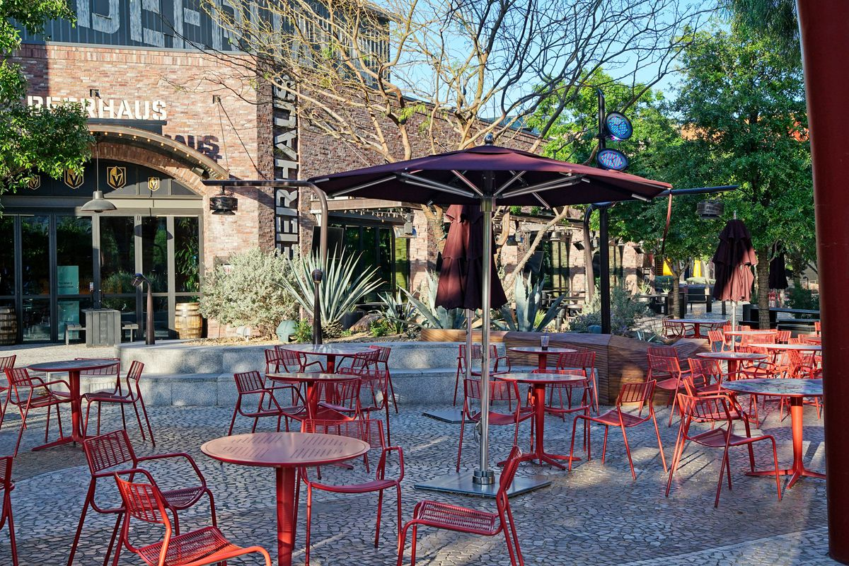 A patio setting with red tables and chairs