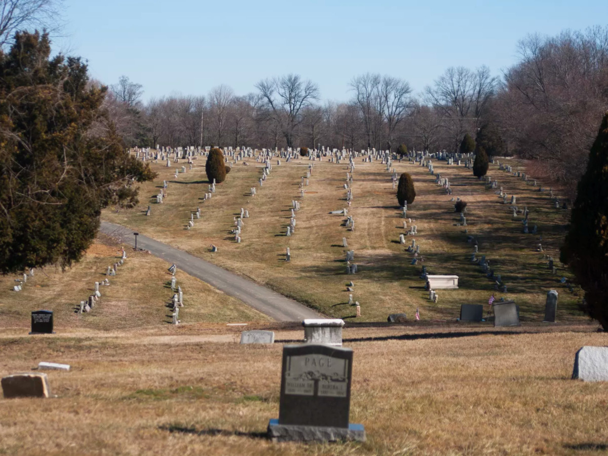 The Eden Cemetery in Philadelphia. There are multiple gravestones in a large field surrounded by trees.