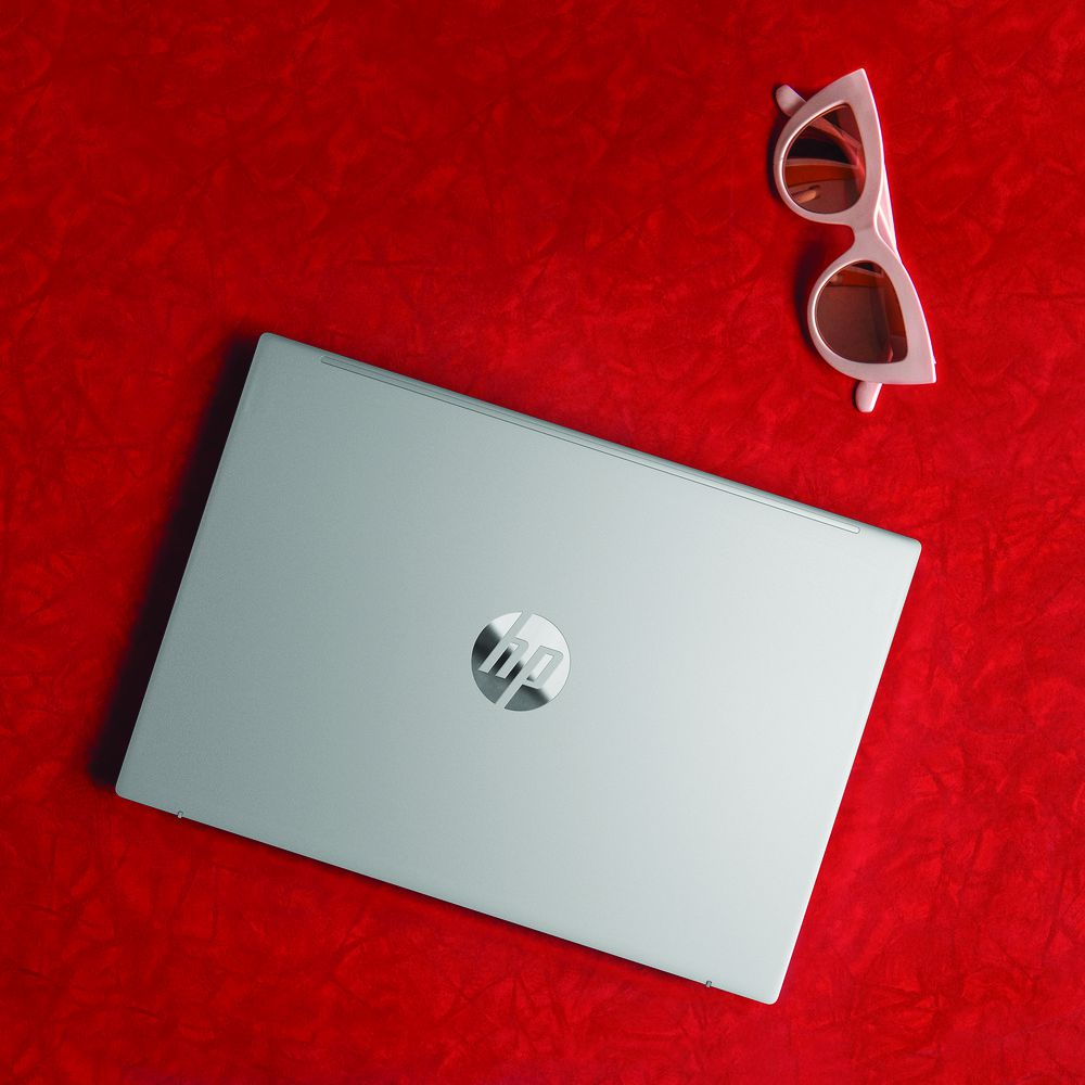 The HP Pavilion Aero 13 closed on a red background. To the right is a pair of pink sunglasses.