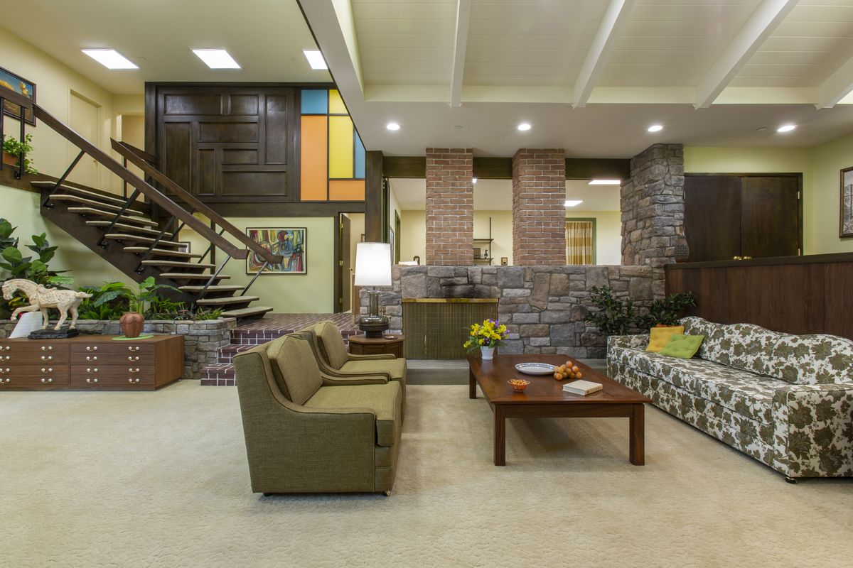 An expansive living room with carpeted floors, a stone and brick fireplace, and floating staircase. Behind the staircase, a wood paneled wall with orange, yellow, and blue inserts.