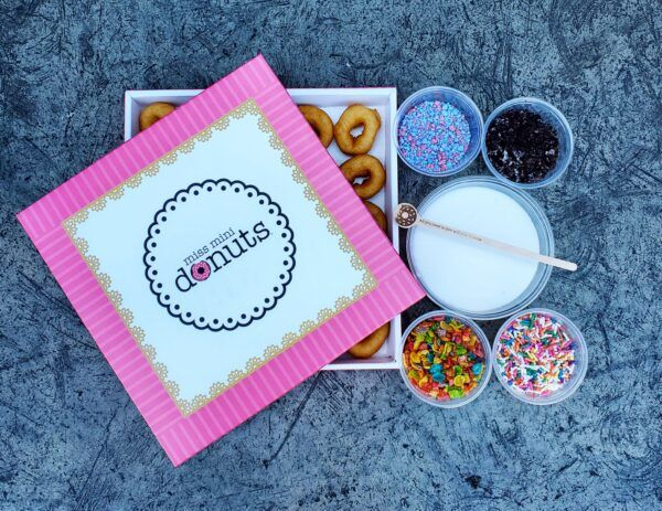 a pink box of tiny donuts alongside containers of white icing, colorful sprinkles and other toppings and candies.