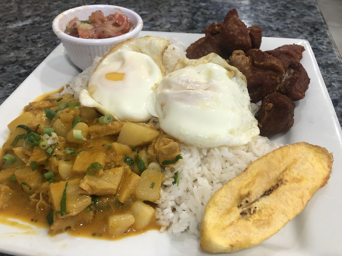 A white square plate filled with a yellow stew, white rice, a yellow slice of plantain, fried pork, two white eggs, and a white cup filled with red vegetables and shrimp.