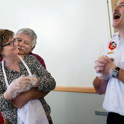 Ed Snoddy hugs his wife, Janice Kimball, executive director of the Housing Authority of the County of Salt Lake, while helping her into an apron as South Salt Lake Battalion Chief Jason Nicholl laughs at Grace Mary Manor in South Salt Lake on Tuesday, Nov. 22, 2016.