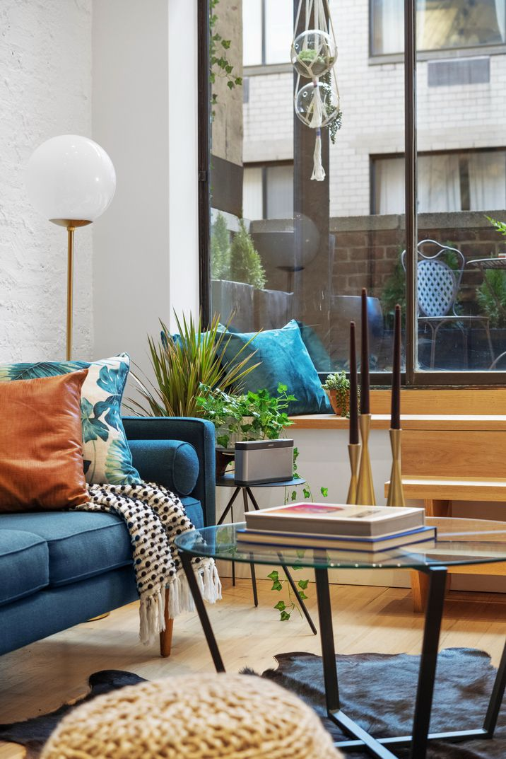 A living room area with a blue couch, a planter, a glass coffee table, and a glass door that leads to a balcony.