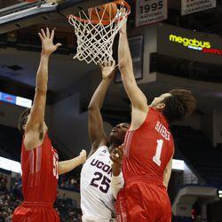 UConn's Josh Carlton (25) puts back in a rebound between two Boston University defenders.