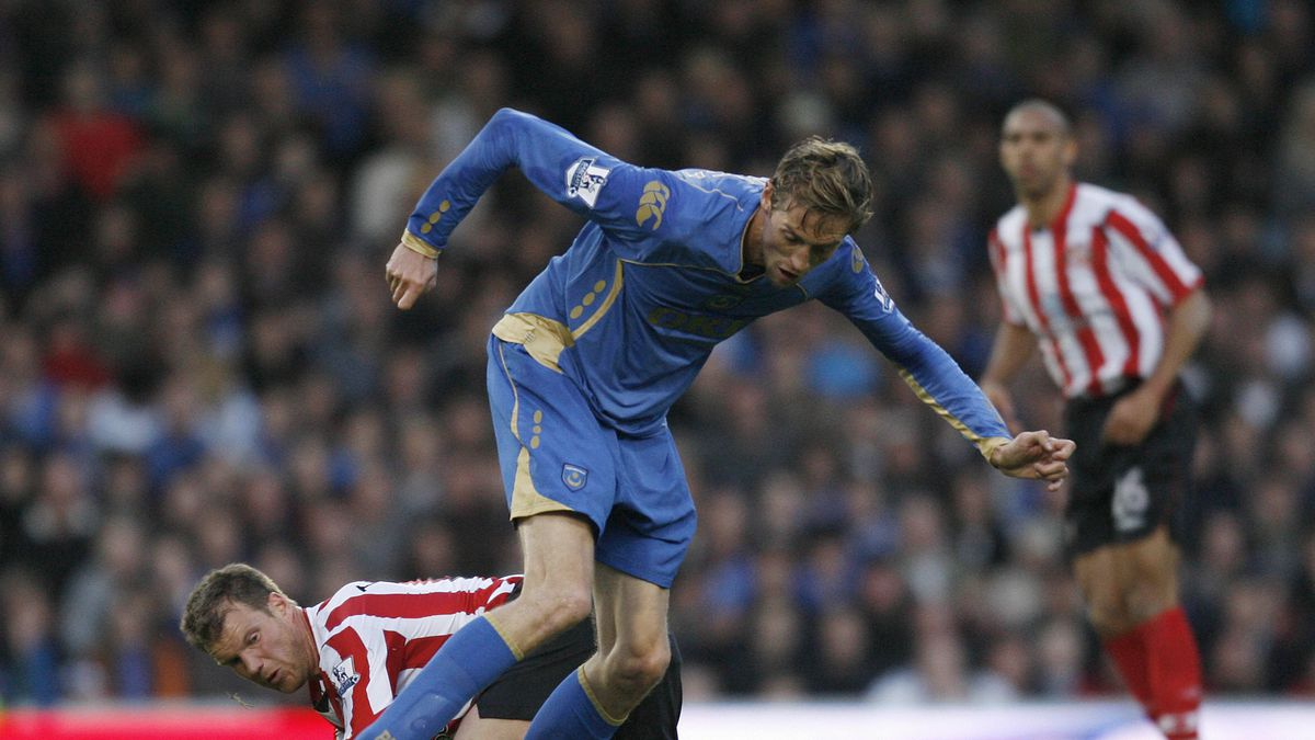 Peter Crouch of Portsmouth (C) vies with