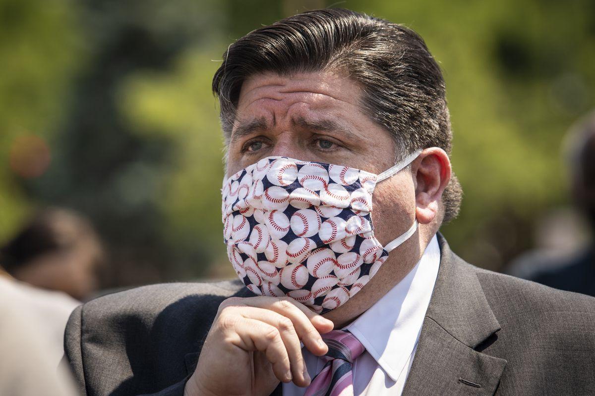 Gov. J.B. Pritzker adjusts his face mask after a news conference in June 2020.
