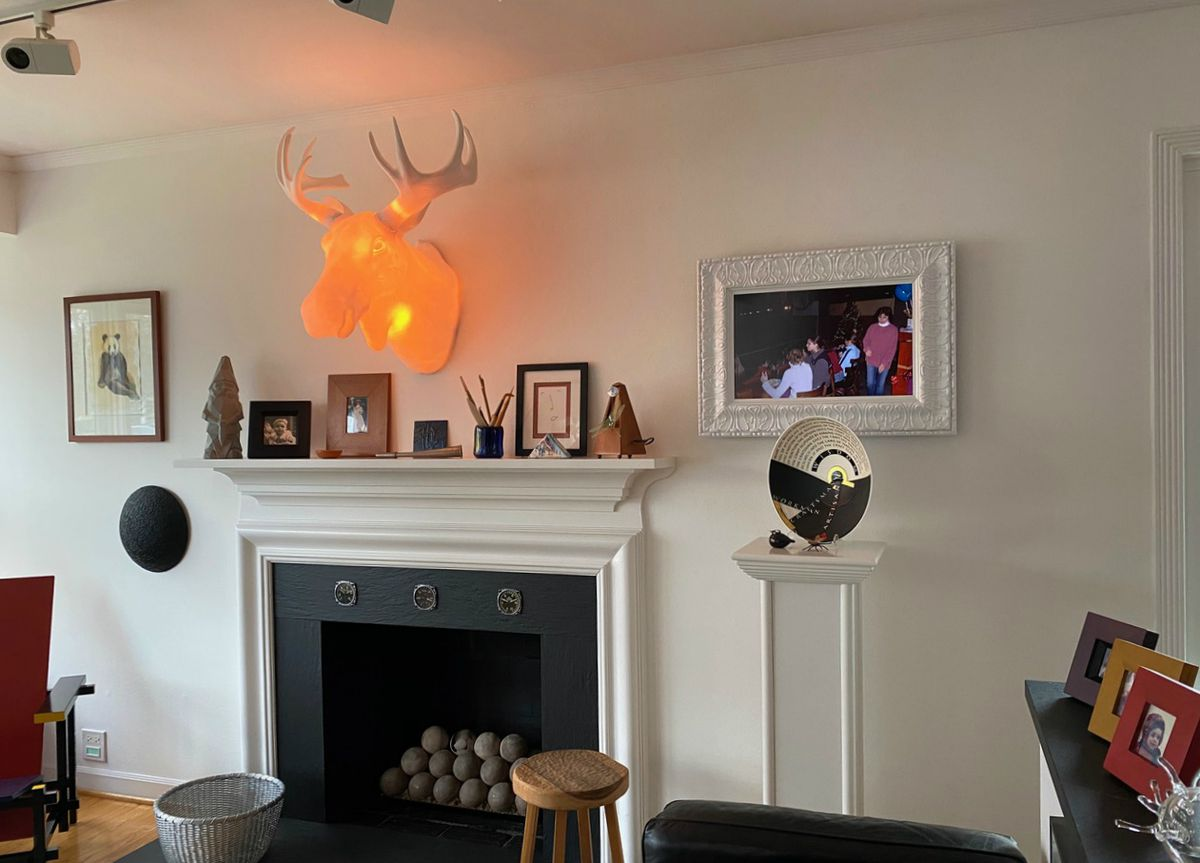 A digital photo frame with ornate white frame hangs on a white wall with a mantel.