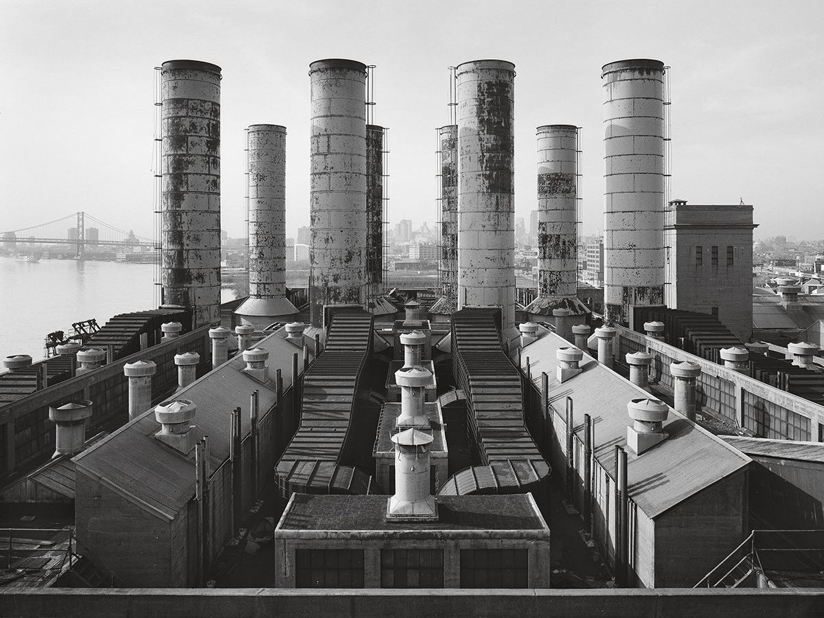 A large abandoned power plant in Philadelphia. There are many smoke stacks and chimneys on the roof.