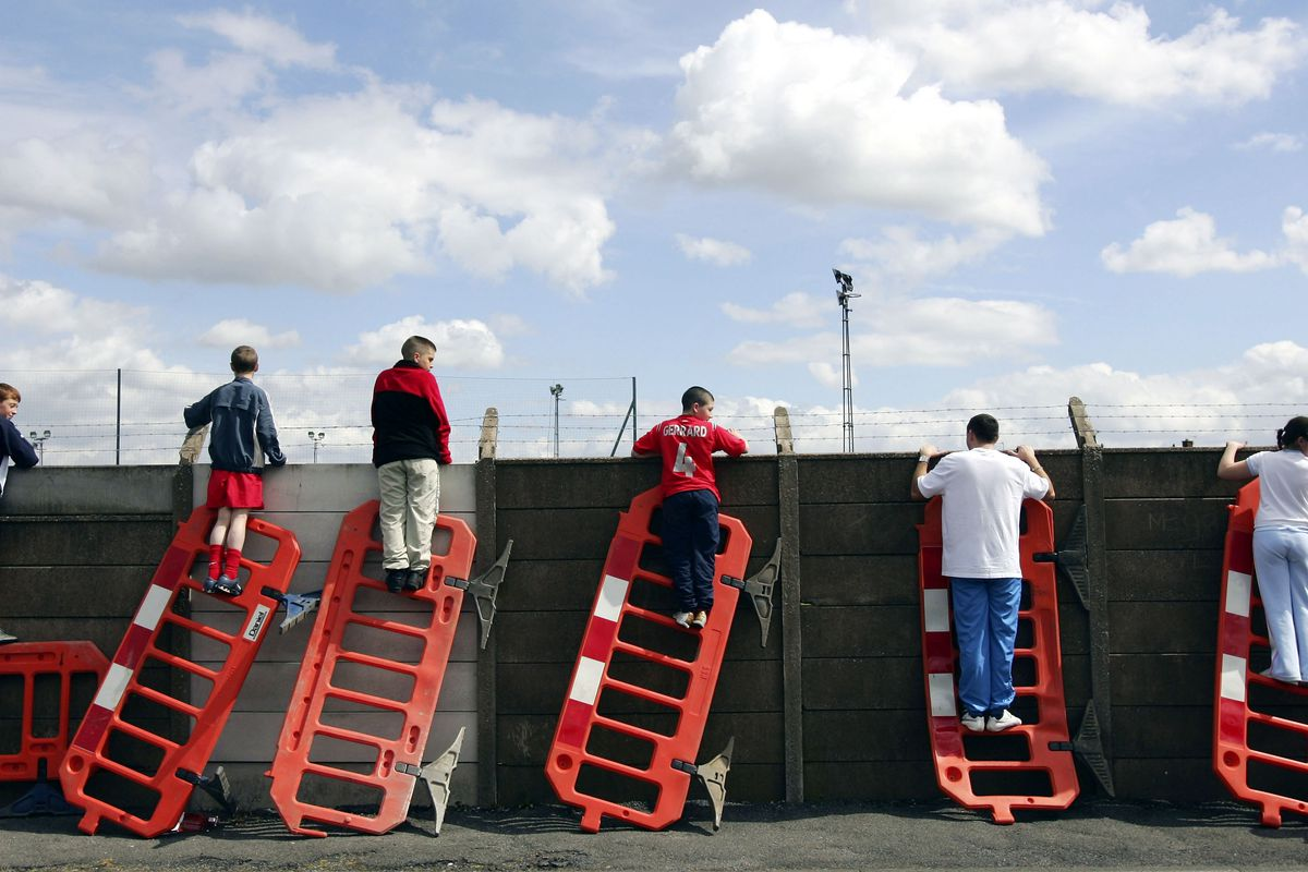 Liverpool fans use roadworks barriers to get a glimpse of the Liverpool team training session ahead of the Champions League Semi Final Second Leg match against Chelsea at Melwood Training Complex on May 2, 2005.