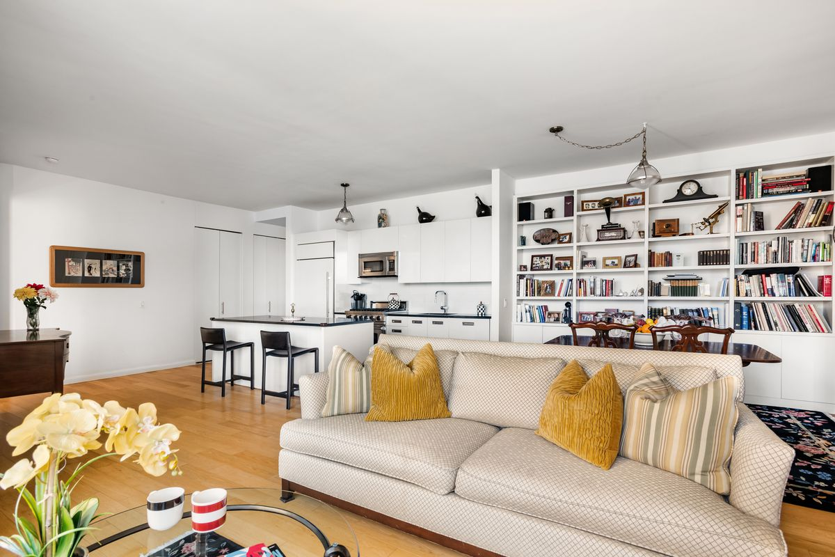 A living room with a beige couch, built-in bookshelves, hardwood floors, and a glass coffee table.
