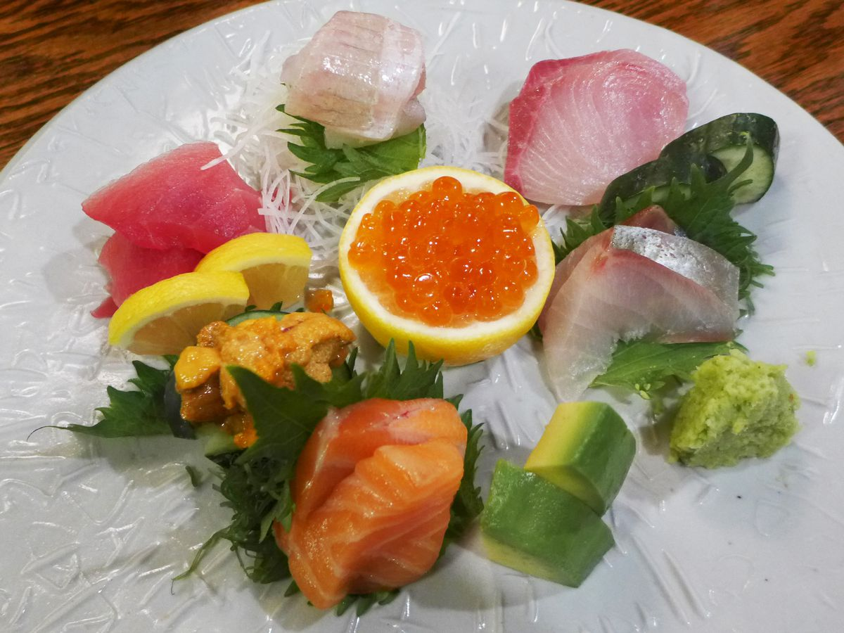 A white plate with 10 or so sashimi selections, including tuna, uni, and mackerel.