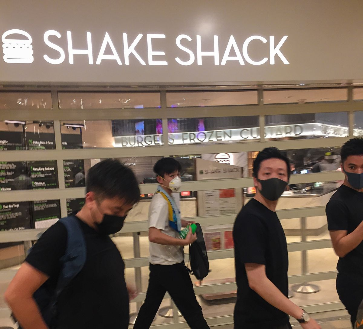 four masked protestors walk by a Shake Shack sign