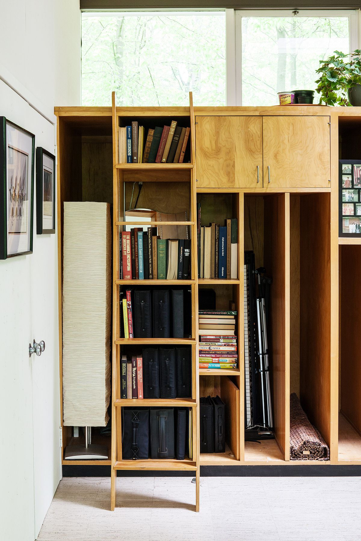 Natural wood shelves and deep cubbies were designed for art supplies and canvases. The new owners use them for books and files. A library ladder helps access upper cabinets.