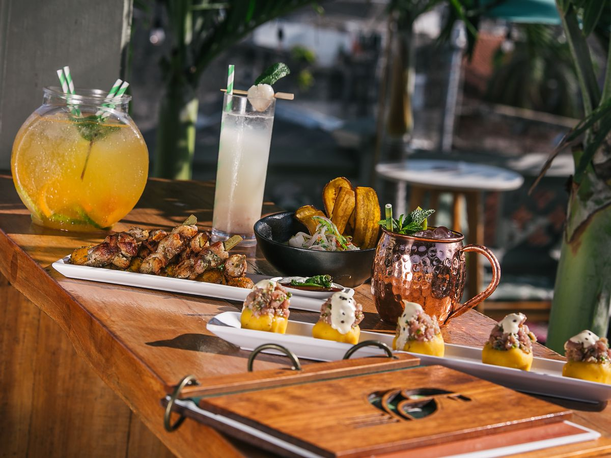 Trays with various bar foods sit on a long wooden bar along with a spiral-bound menu, several cocktails in different glassware, and a large punch bowl