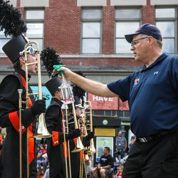An aid sprays water into a student's mouth as the Timpview High School Marching Band performs during the Grand Parade in Provo on Monday, July 5, 2021.