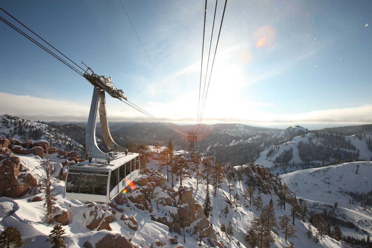 Aerial view of the Squaw Valley tram as it travels on cables suspended over snow-covered mountains.
