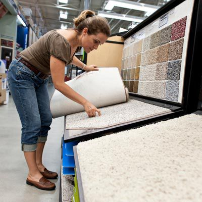 Person taking a look at a carpet sample in a store.