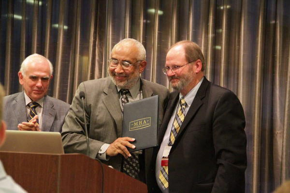 Darius Gray, center, displays the special citation given to him by Ronald O. Barney, right, executive director of the Mormon History Association. Richard E. Bennett, left, this year's association president, applauds.