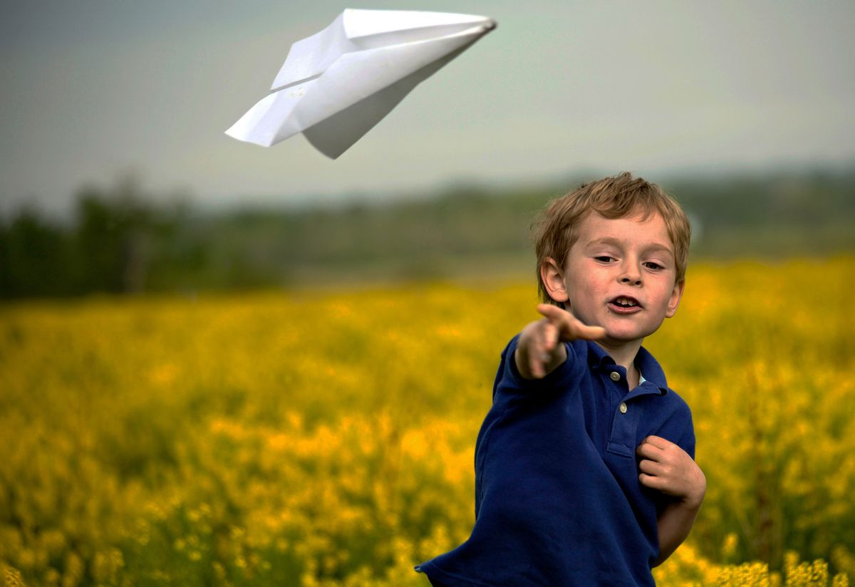 A kid plays with a paper airplane. He's part of a surprisingly long tradition. (Shutterstock)