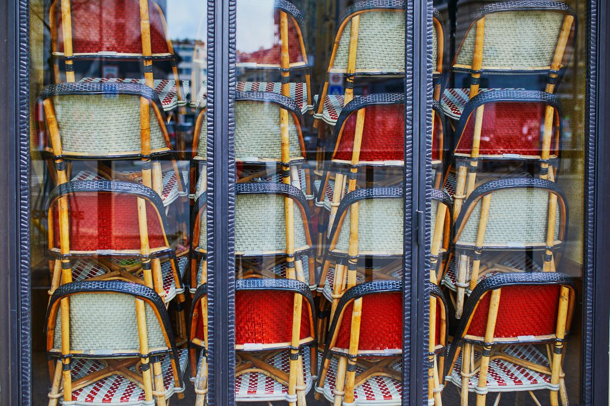 Seen through a glass window, stacks of wicker chairs obscure the view within.