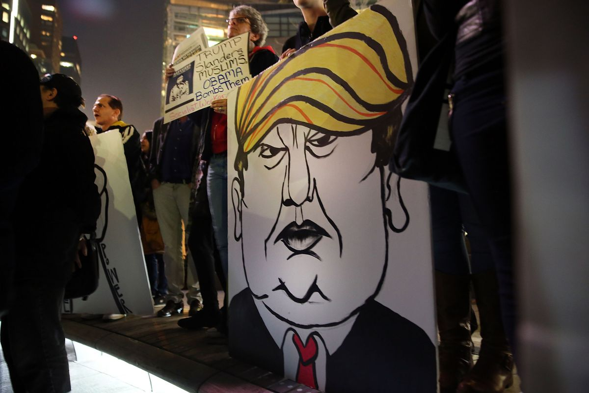 A protester holds a caricature of  presidential candidate Donald Trump during a demonstration against racism and Trump's recent remarks concerning Muslims on December 10, 2015, in New York City.