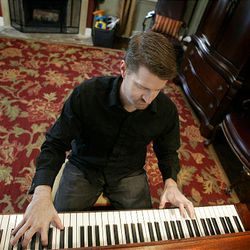 Musician Ryan Stewart plays piano in his home in Salt Lake City Tuesday. On Thursday, Stewart's debut album went on sale.