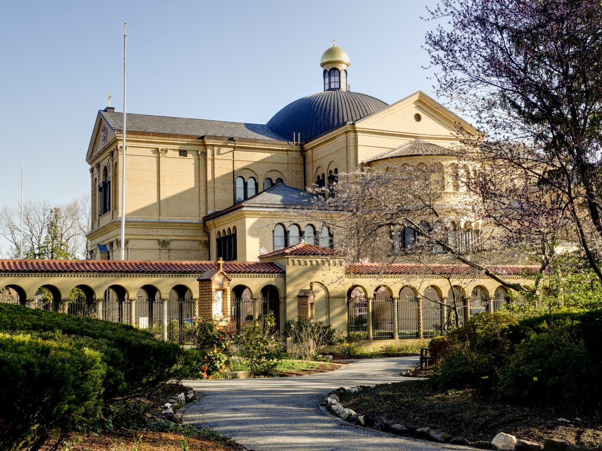 The exterior of the Franciscan Monastery of the Holy Land in America. The facade is ivory with a blue roof and columns.