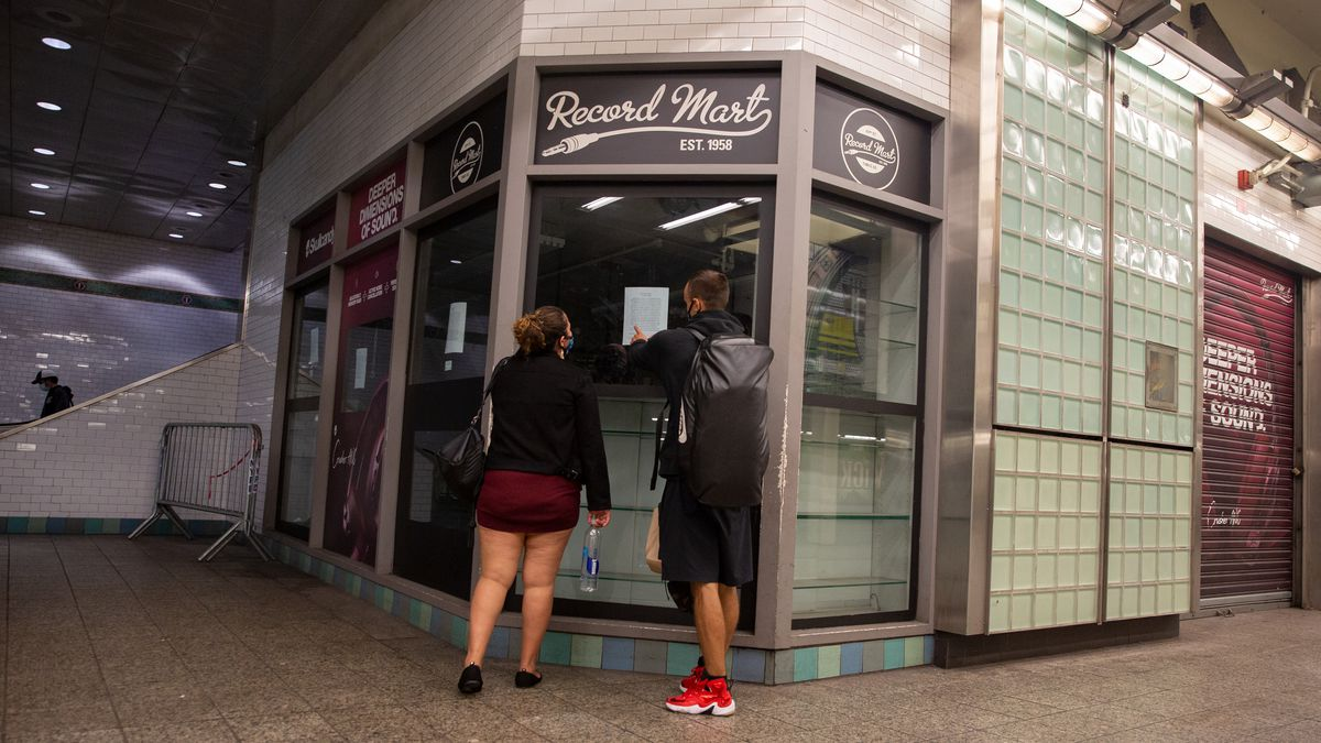 A couple reads a note on the shuttered Record Mart in the Times Square station, Aug. 31, 2020.